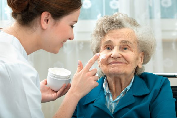 Carer applying face cream to elderly