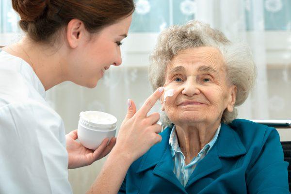 Carer applying face cream to elderly